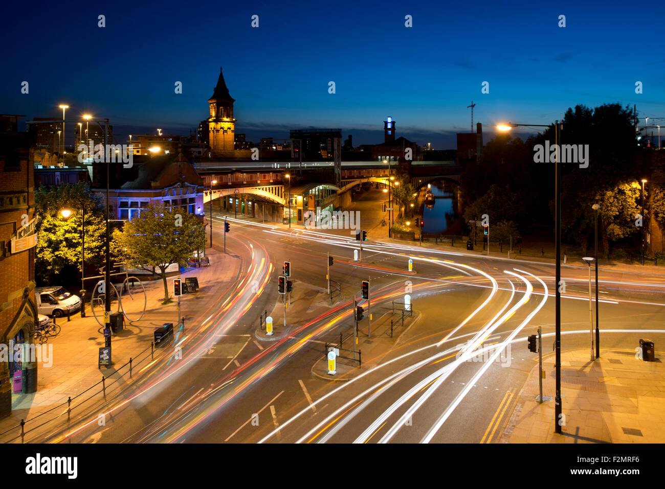 Light trails of moving traffic at the junction of Whitworth Street West and Deansgate in Manchester city centre - Stock Image