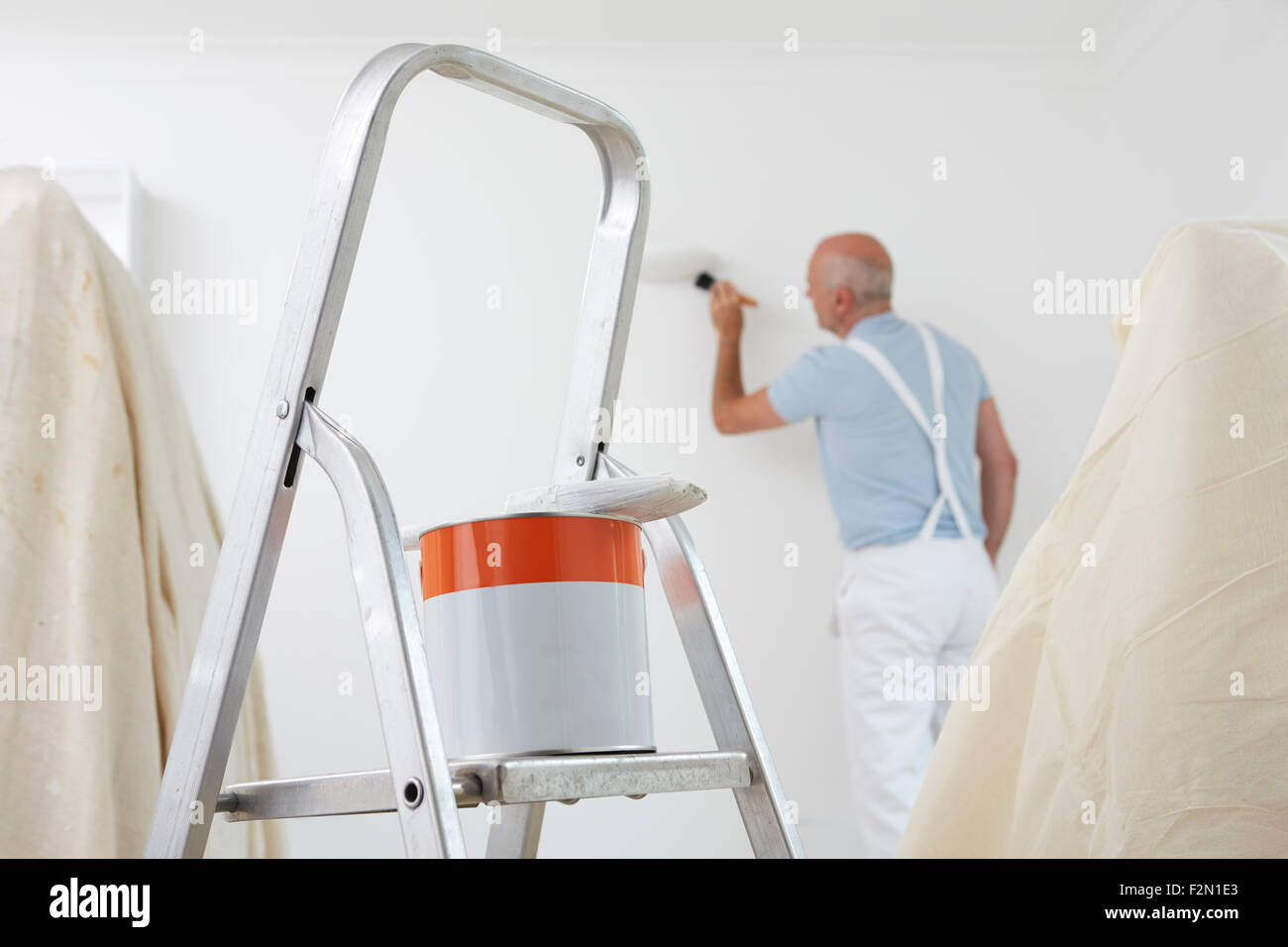 Man Decorating Room With Can Of Paint And Brush In Foreground - Stock Image