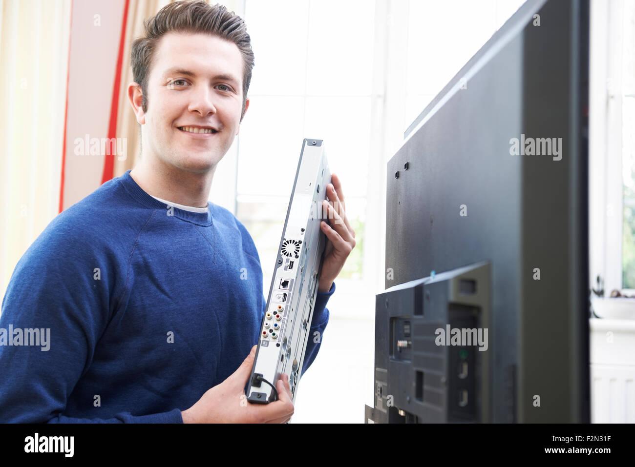 Portrait Of Engineer Installing Digital TV Equipment - Stock Image