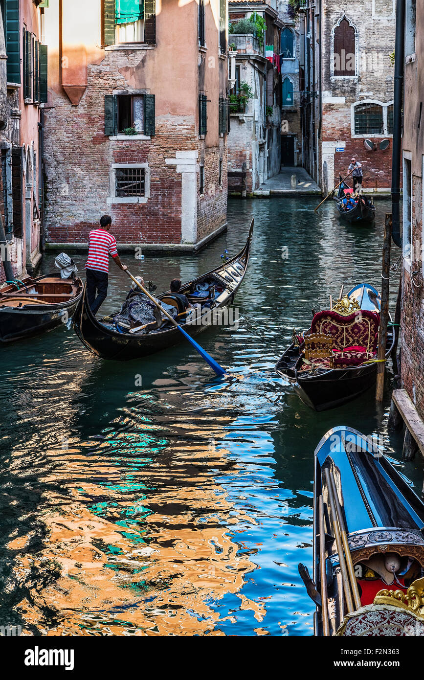 Gondolier provides tourists with an intimate tour of the city, Venice, Italy - Stock Image