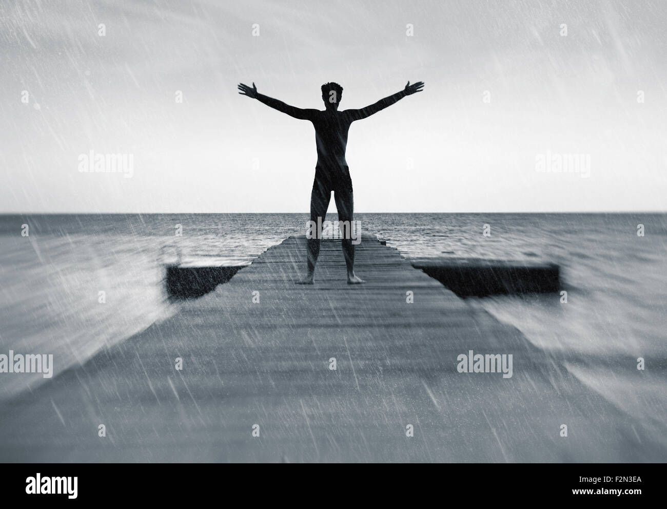 Freedom in nature concept - free happy man in the rain - Stock Image