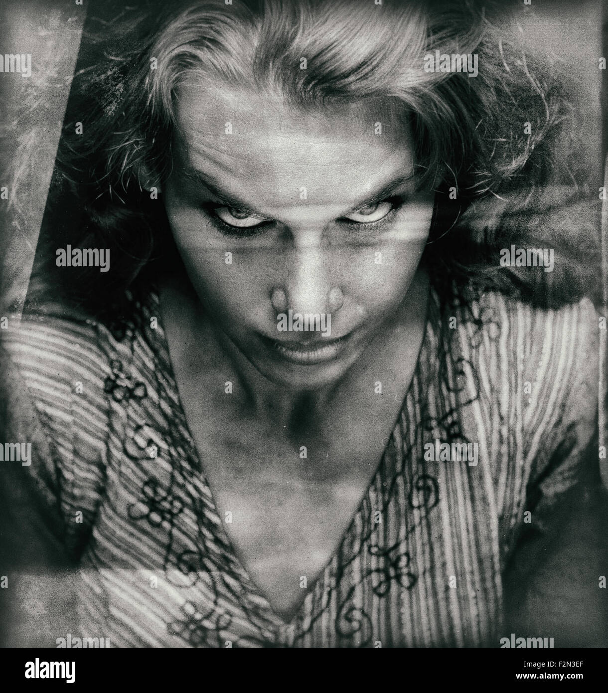 Vintage portrait of scary woman with evil looking face - Stock Image