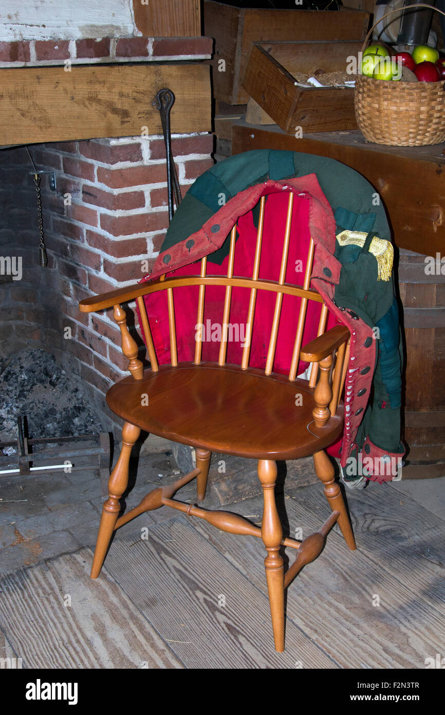 An American Loyalist uniform jacket hanging on the back of a colonial Windsor chair at Fort Stanwix In Rome New - Stock Image