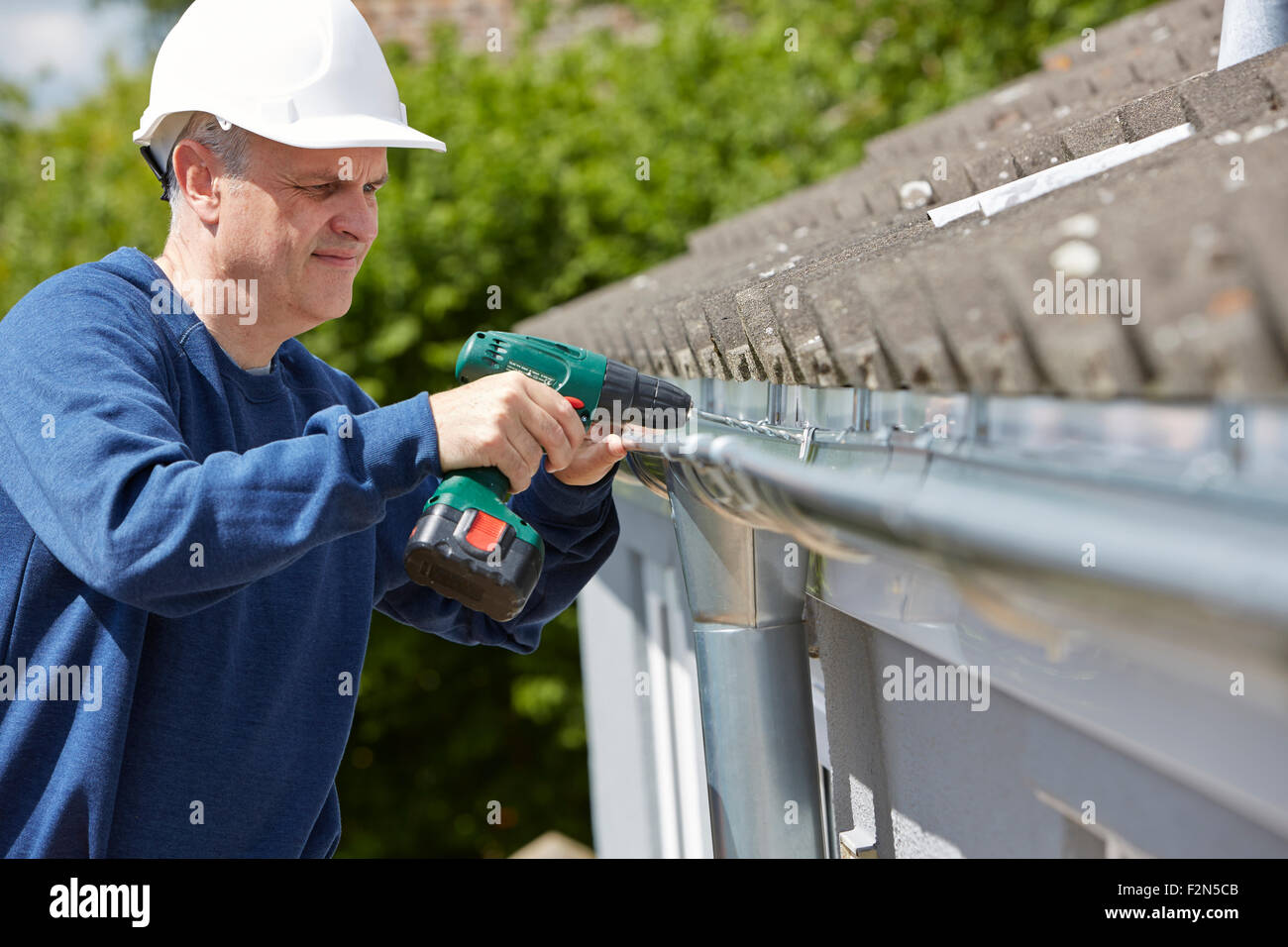 Workman Replacing Guttering On Exterior Of House - Stock Image