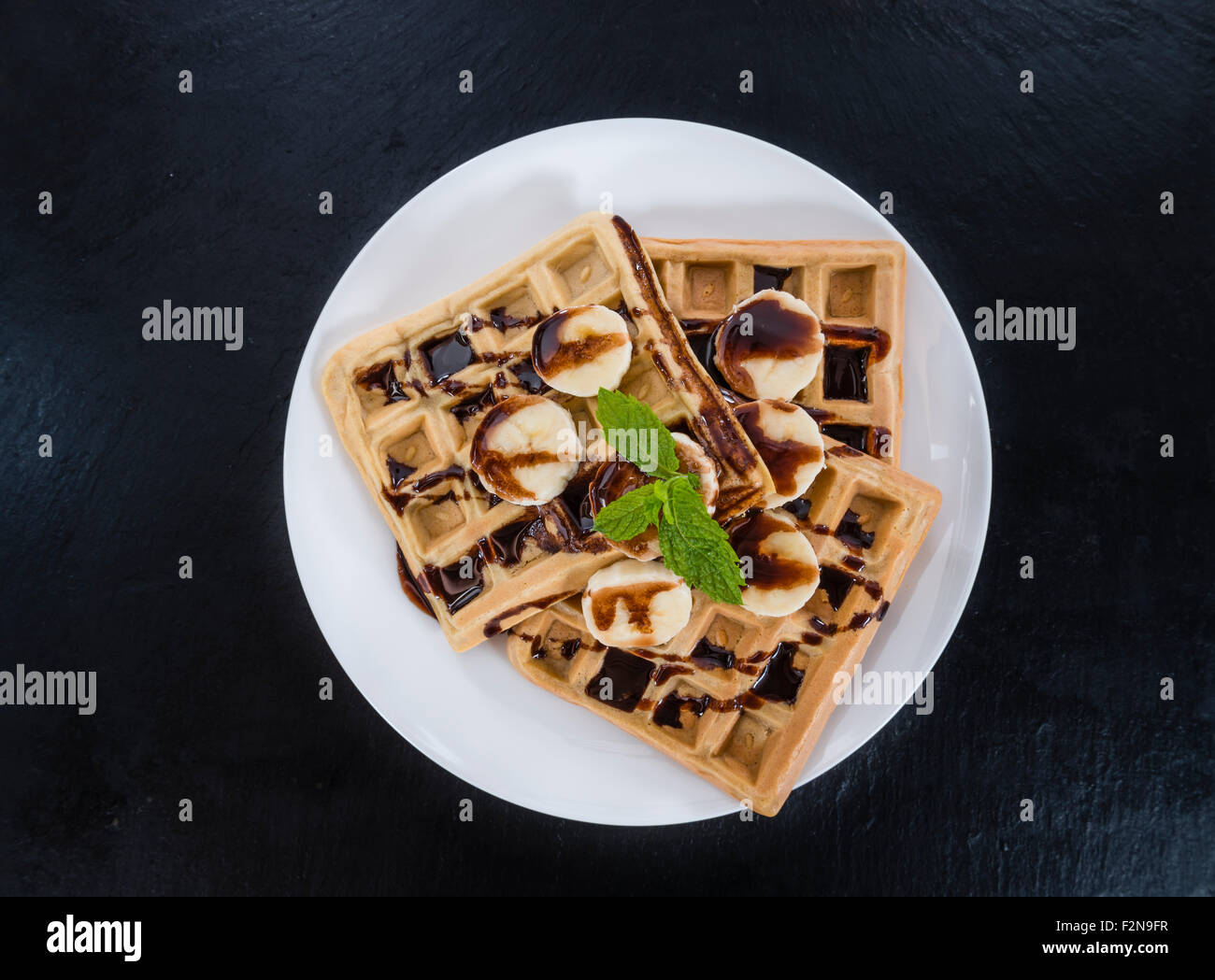 Waffles with Bananas and Chocolate Sauce (close-up shot) - Stock Image