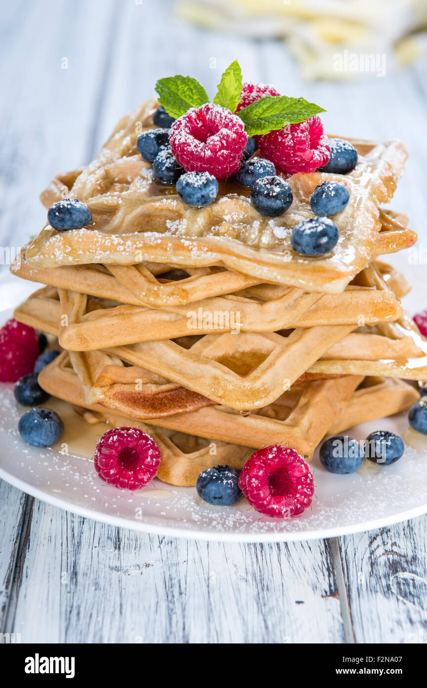 Fresh made Waffles with mixed Berries and Honey (close-up shot) - Stock Image