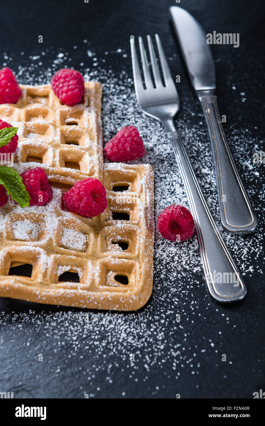 Homemade Waffles with Raspberries and powder sugar (close-up shot) - Stock Image