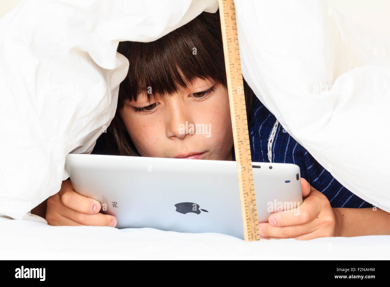 Caucasian male 11 year old child, laying under duvet on bed, looking at i-pad, concentrating studying. Kazki - Stock Image