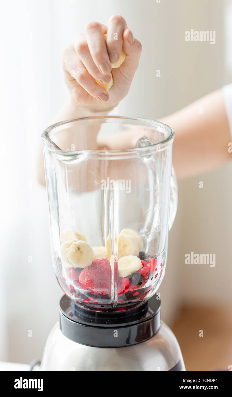close up of woman hand adding fruits to blender - Stock Image