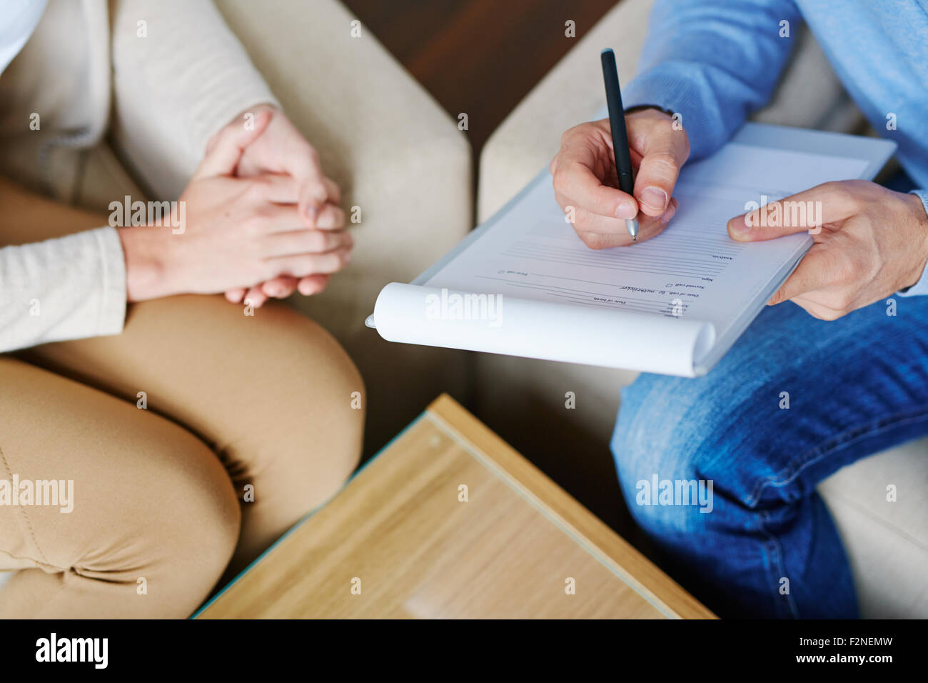 Hands of psychiatrist filling in medical document with patient near by - Stock Image