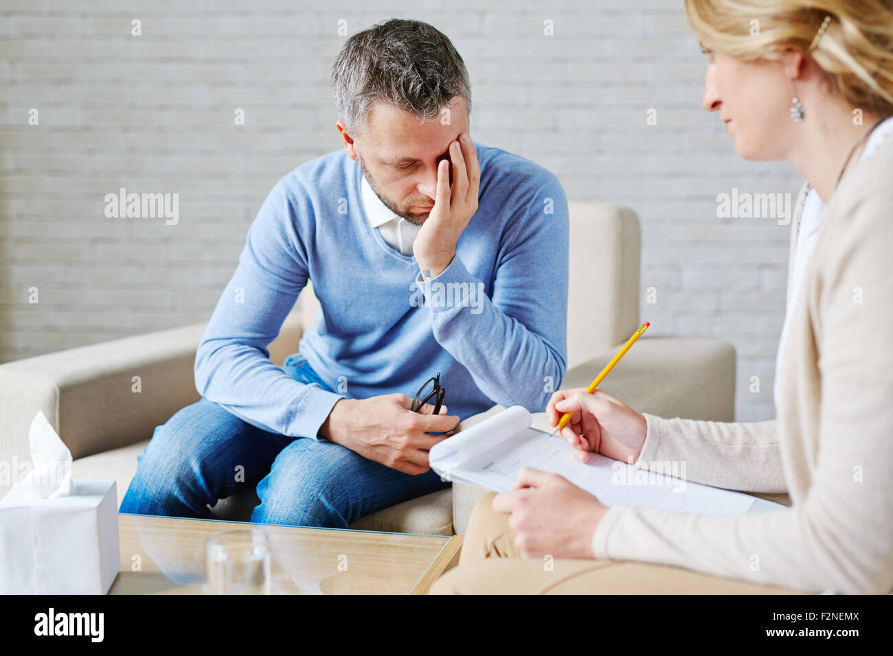 Unhappy patient visiting his psychologist - Stock Image