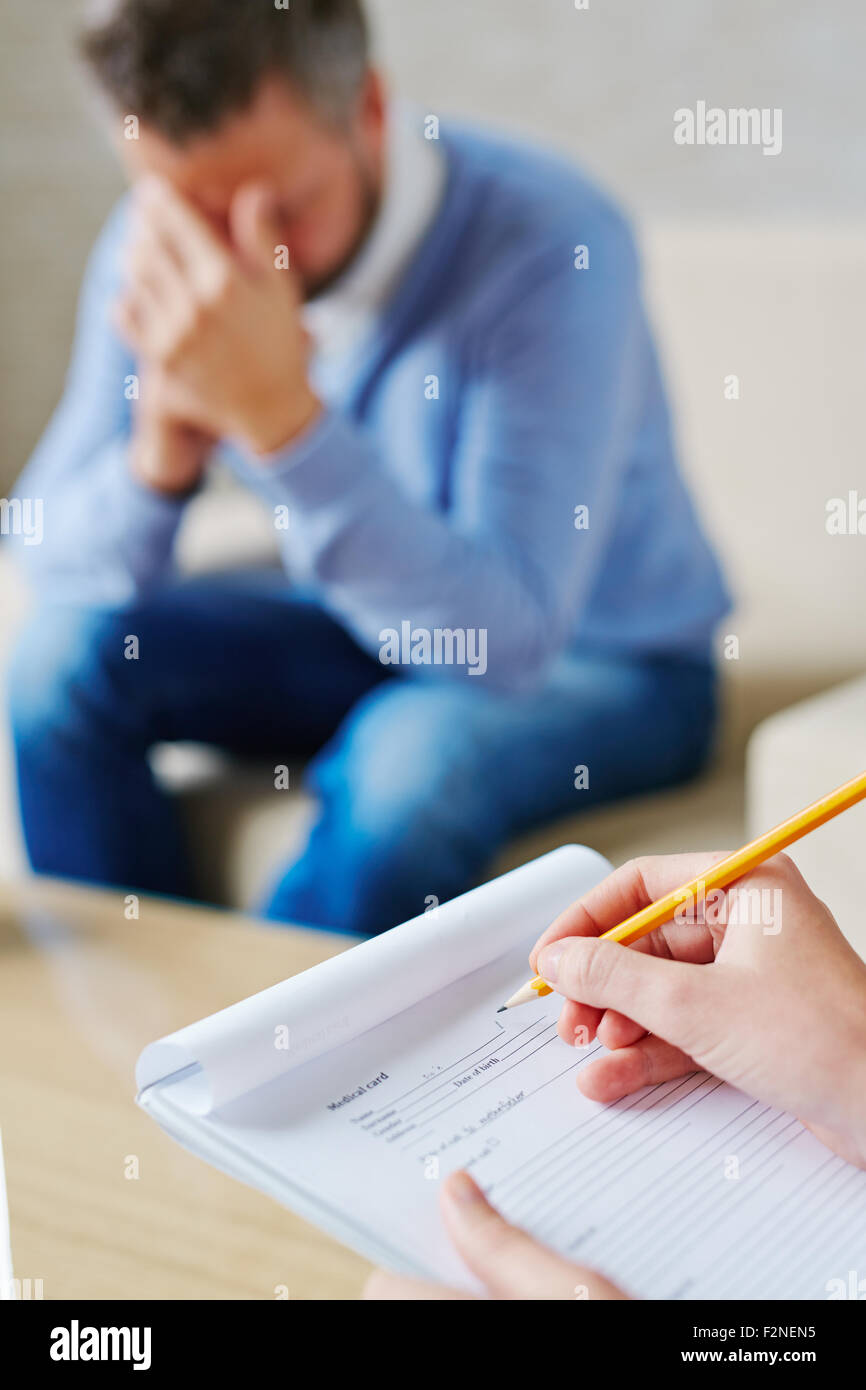 Hands of psychiatrist filling in medical document in front of stressed patient - Stock Image