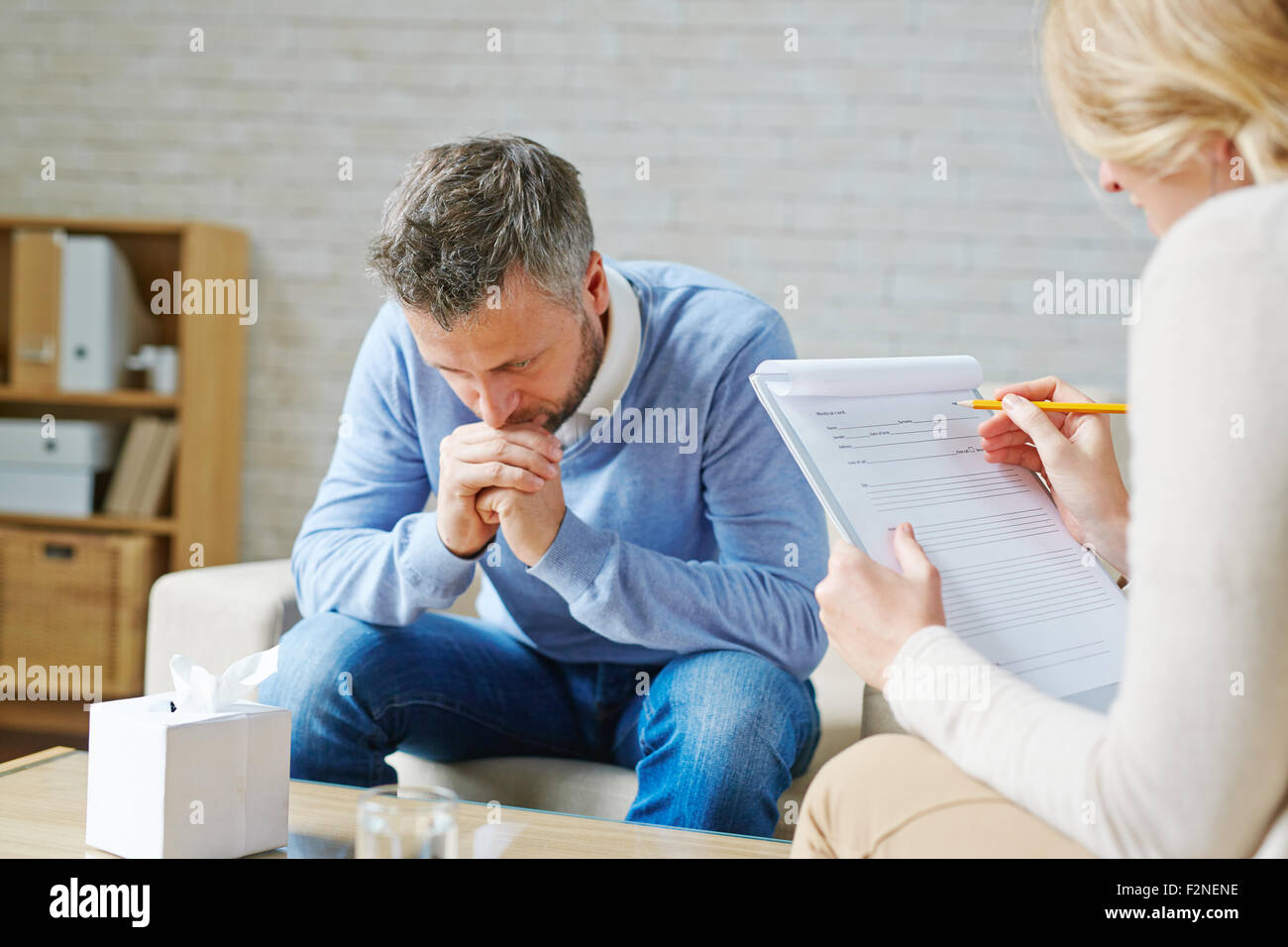 Tense man visiting his psychologist - Stock Image