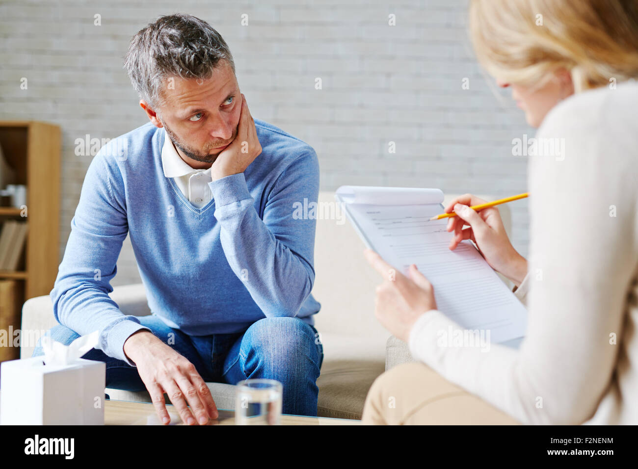Tense man looking at his psychologist during consultation - Stock Image