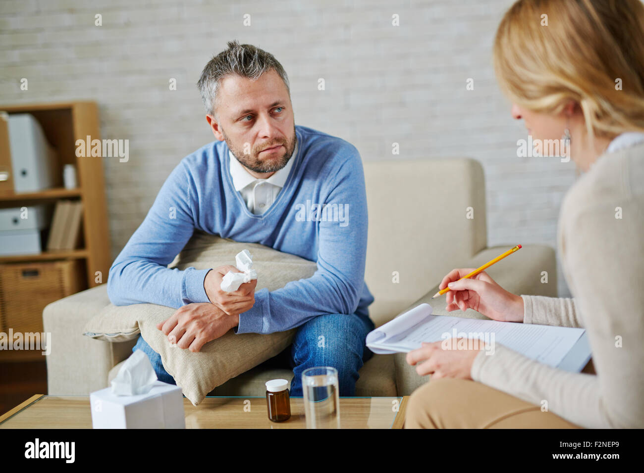 Despaired man with pillow and handkerchief looking at his psychologist during consultation - Stock Image