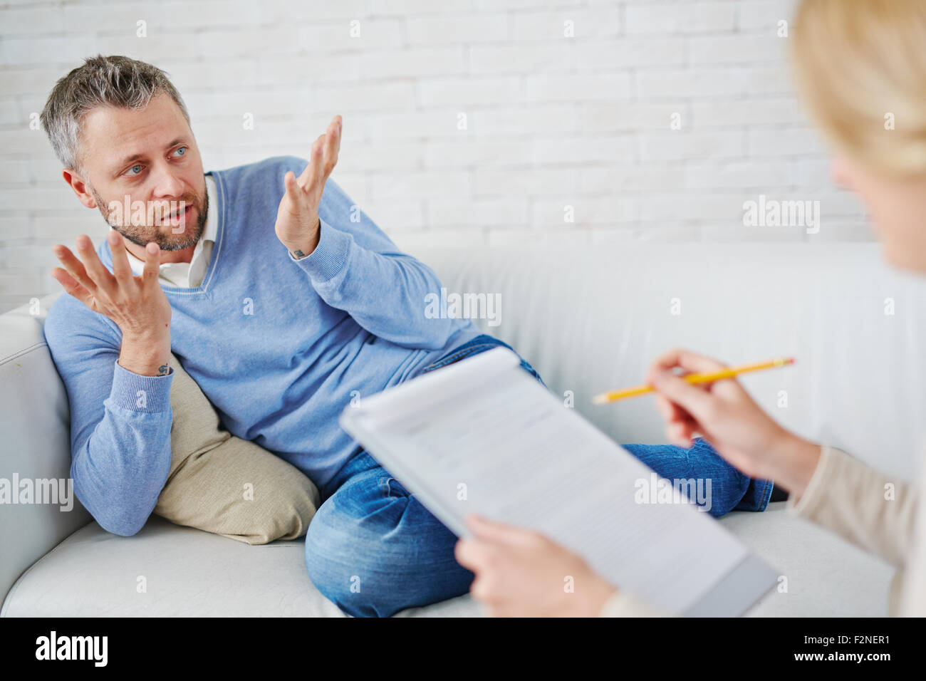 Confused man on sofa telling his psychologist what happened - Stock Image