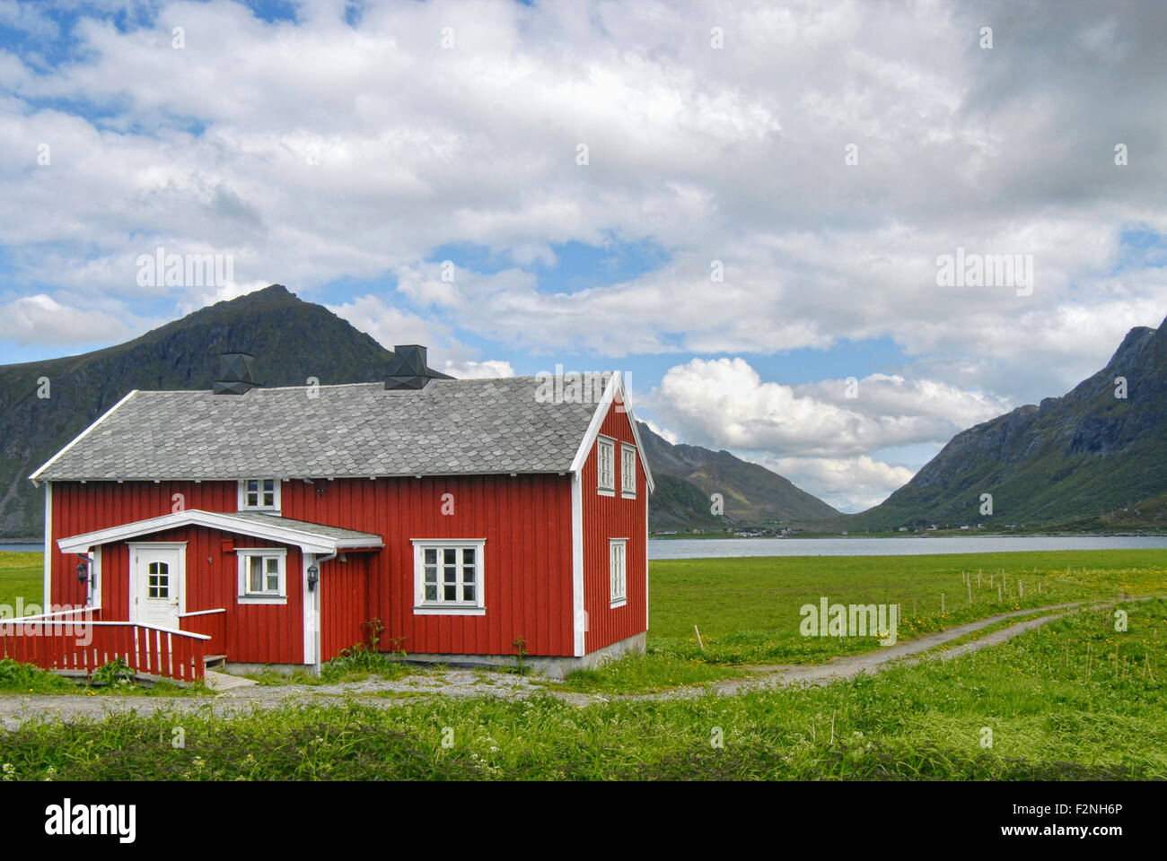 Green farmland with a typically red colored Scandinavian House at the Lofoten Islands, Norway - Stock Image