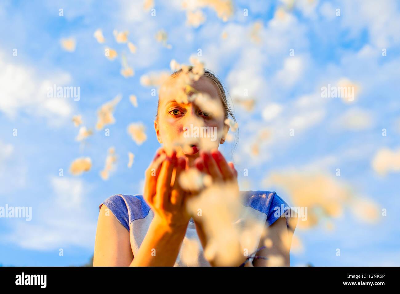 Caucasian teenage girl blowing flower petals under blue sky Stock Photo