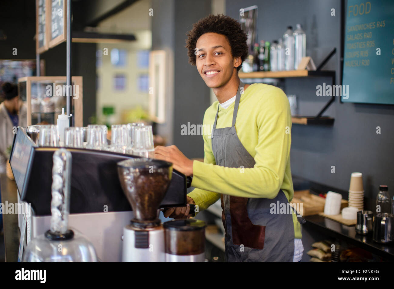 Mixed race barista working in coffee shop Stock Photo