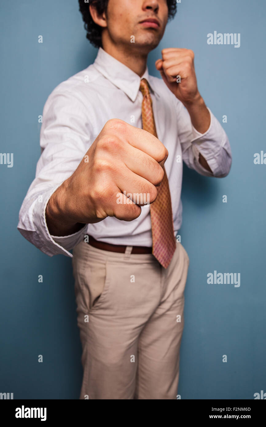 Young man standing by a blue wall throwing punches - Stock Image