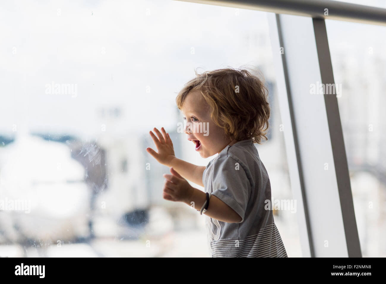 Caucasian baby boy looking out airport window Stock Photo