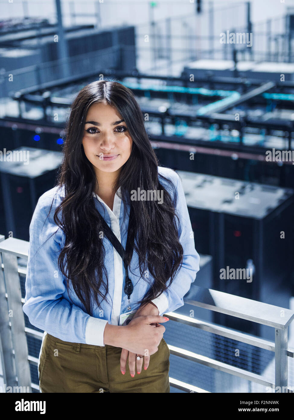 Mixed Race Businesswoman Smiling On Balcony Over Server Room Stock Photo Alamy