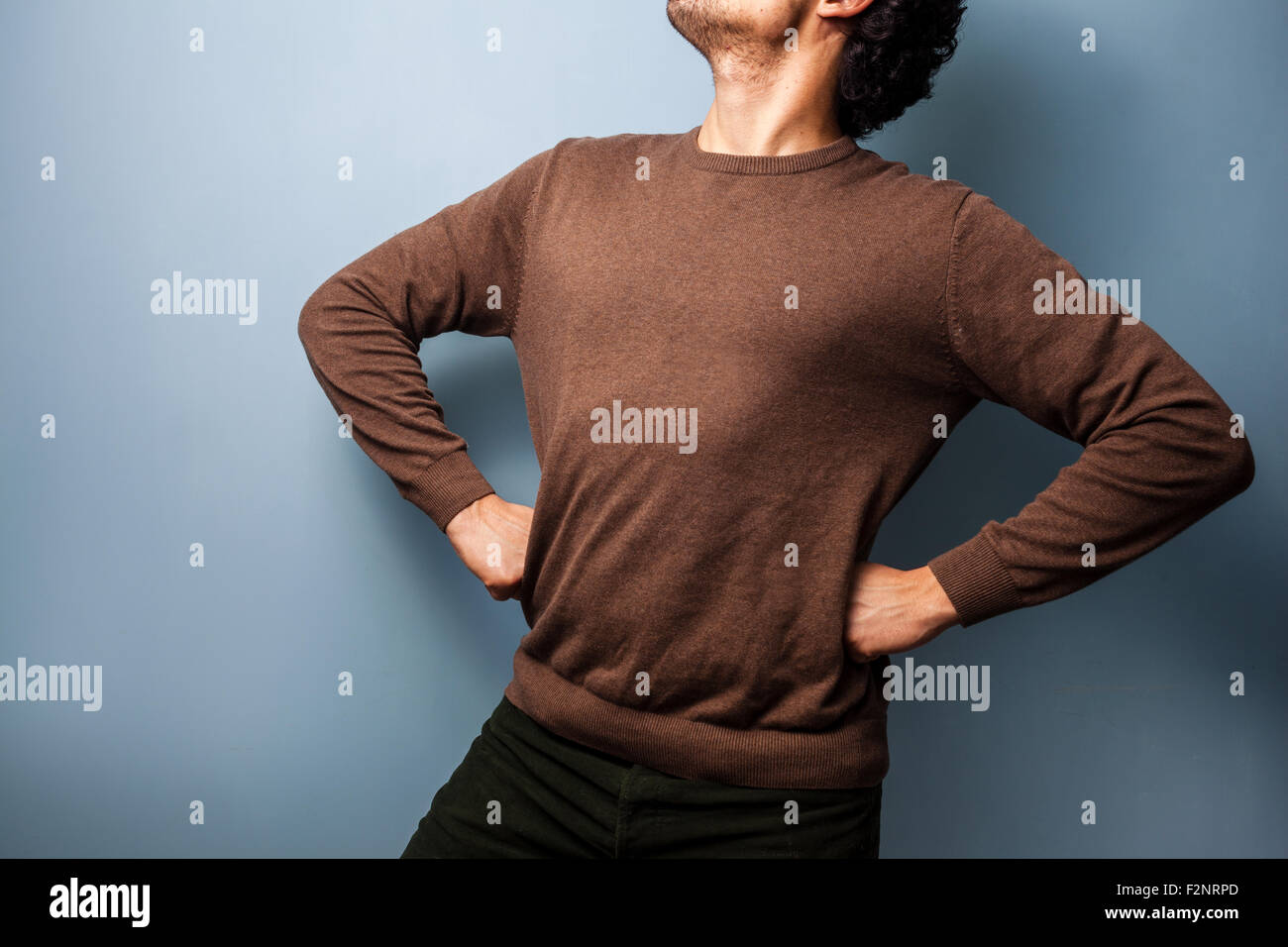 an anonymous young man is standing proudly with his hands on his hips. - Stock Image