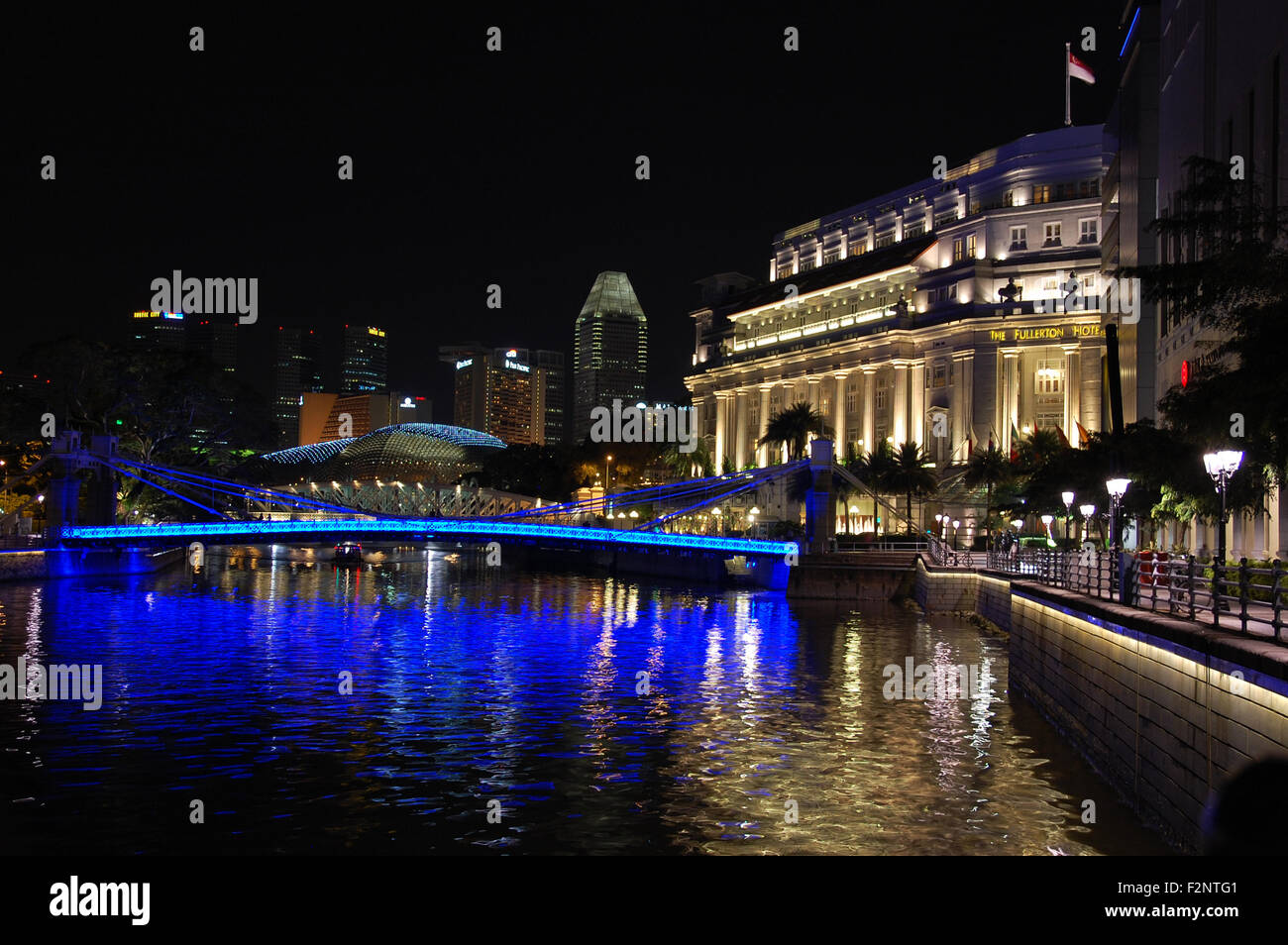 Night with a blue illuminated Cavenagh Bridge spanning the Singapore River and the Fullerton Hotel in Singapore. - Stock Image
