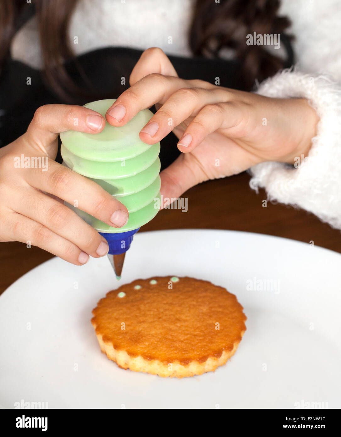 Hands of a girl decorating cakes - Stock Image