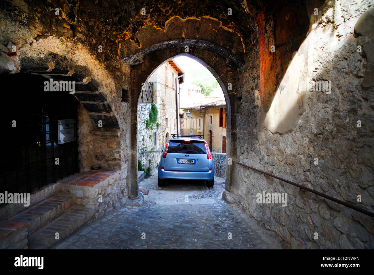 A car negotiates the tight streets in the medieval village of Fontecchio in Italy. - Stock Image
