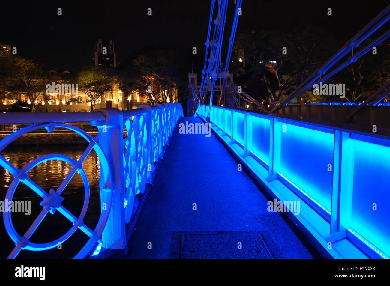 Walkway on the Cavenagh Bridge illuminated blue at night, Singapore - Stock Image