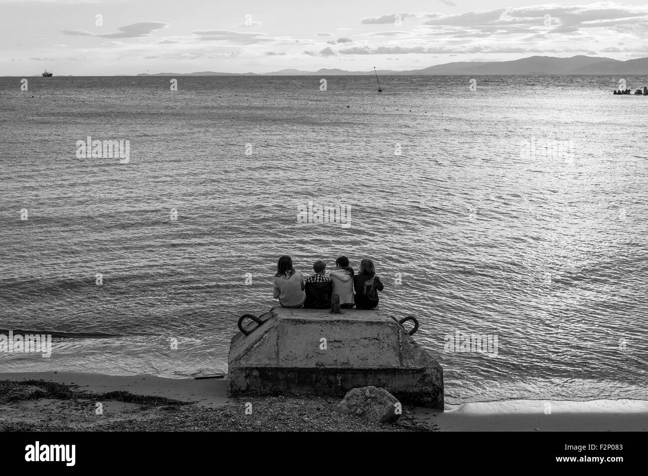 Friends Watching the Sunset at the Beach - Stock Image