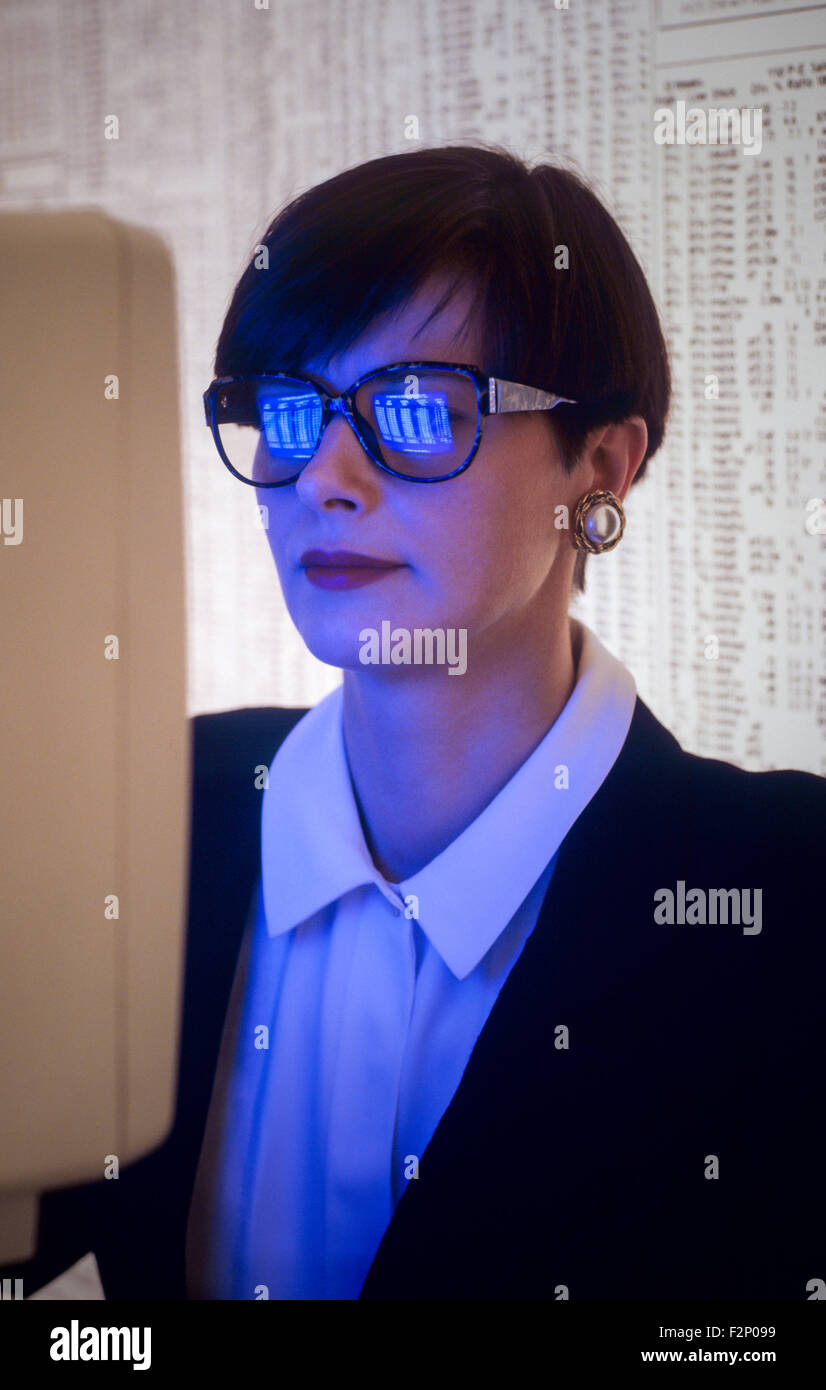 Businesswoman woman with computer screen reflected in her glasses - Stock Image