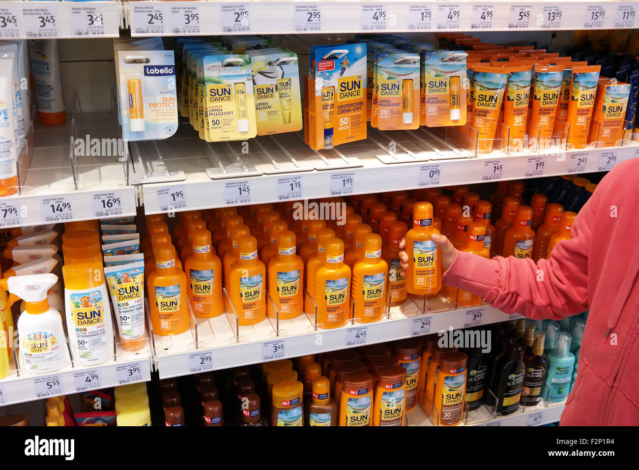 Shelves with home brand sunscreen in a Dm-drogerie markt store. - Stock Image