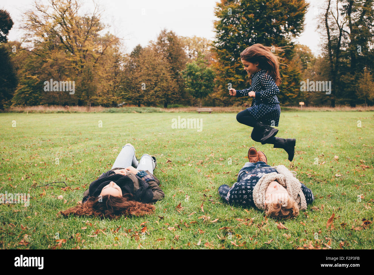 Young parents lying on a meadow while little girl jumping over them in a park Stock Photo