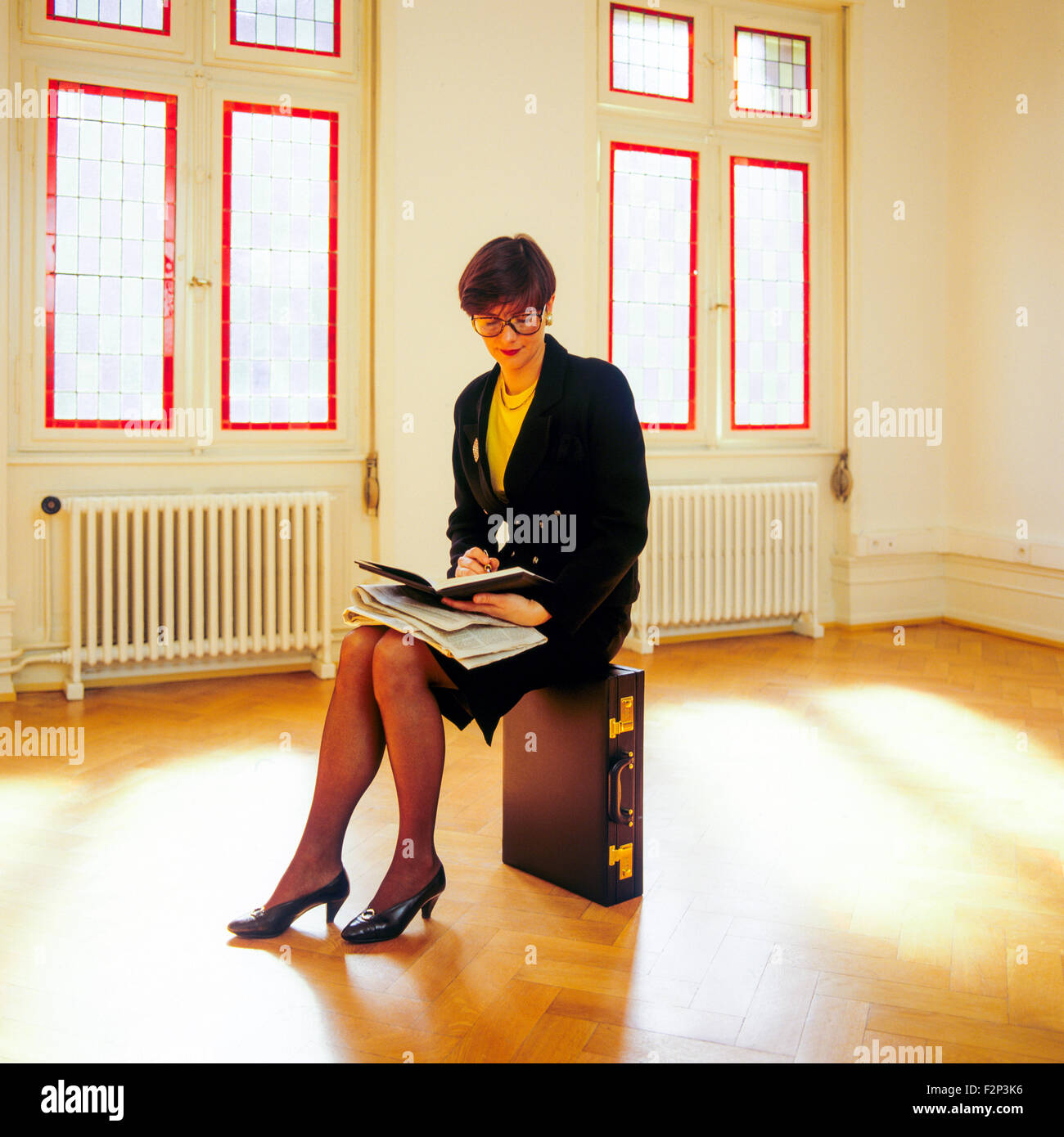 Real estate agent sitting on her briefcase in an empty room - Stock Image
