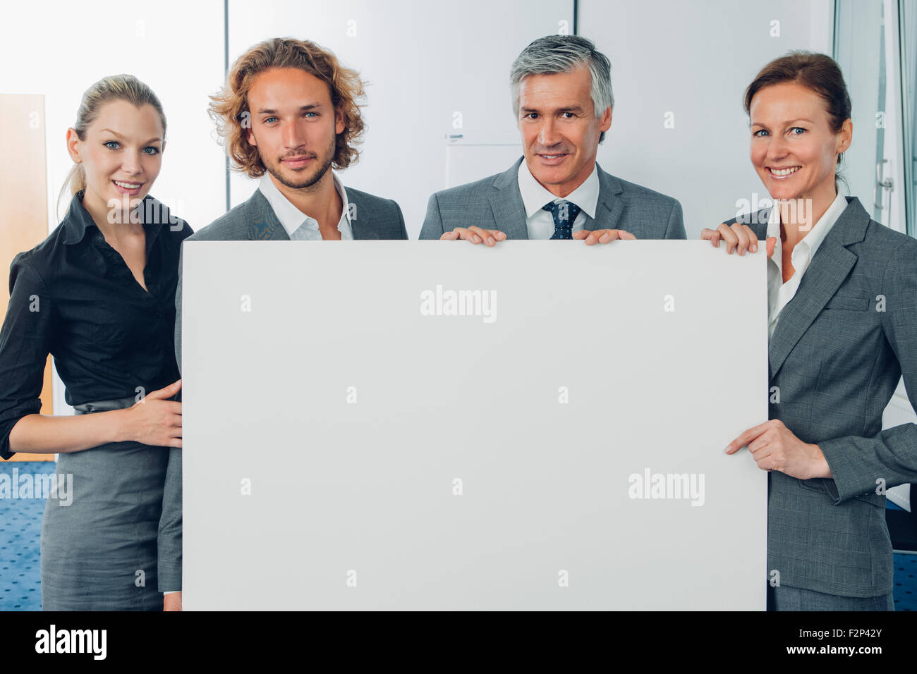 Portrait of happy business team holding a blank billboard while at office - Stock Image