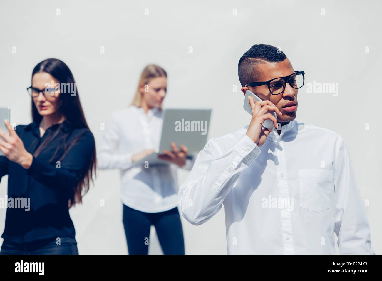 Young man telephoning with smartphone in front of two other people - Stock Image