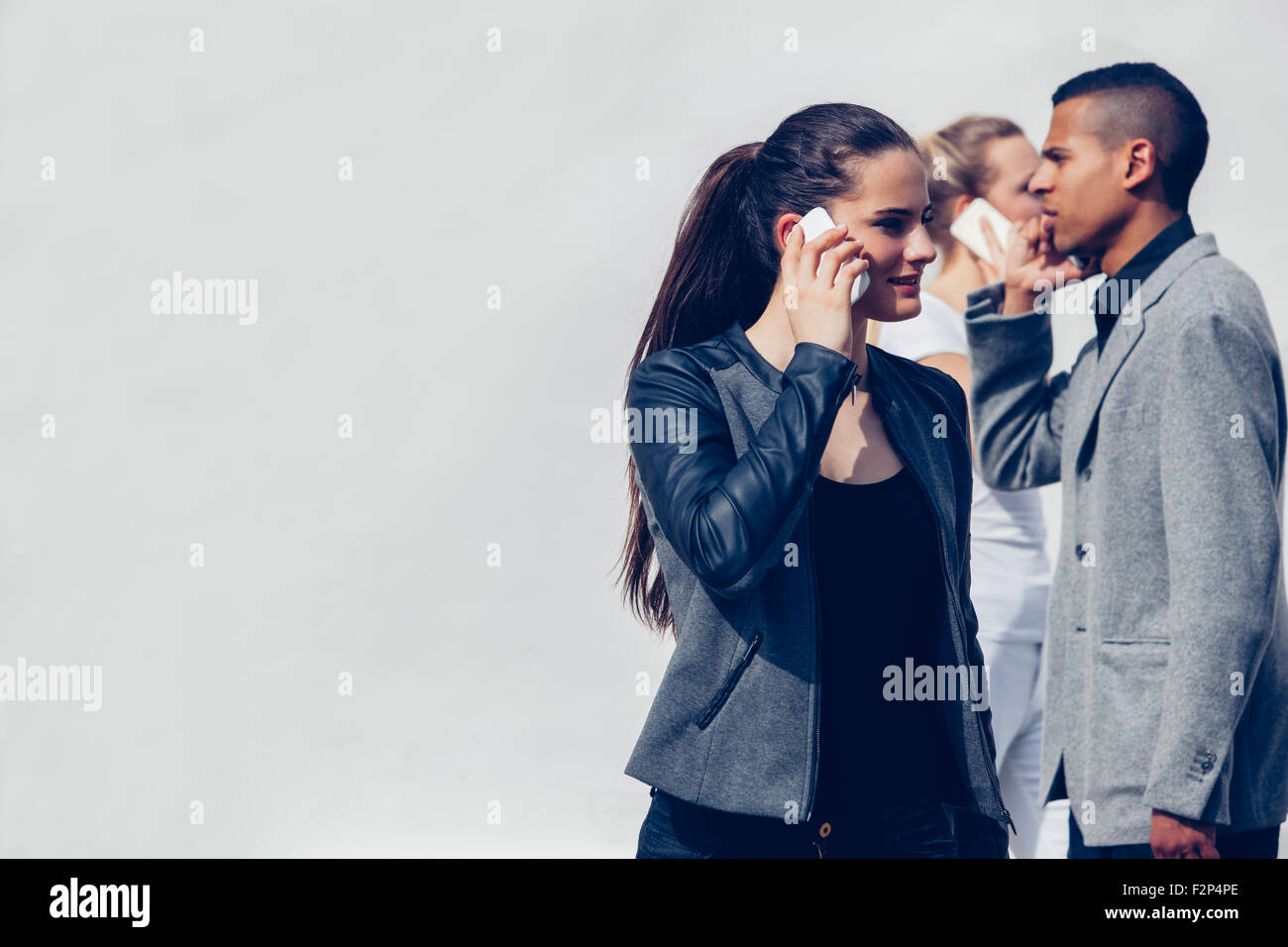 Young woman telephoning with smartphone in front of two other people - Stock Image