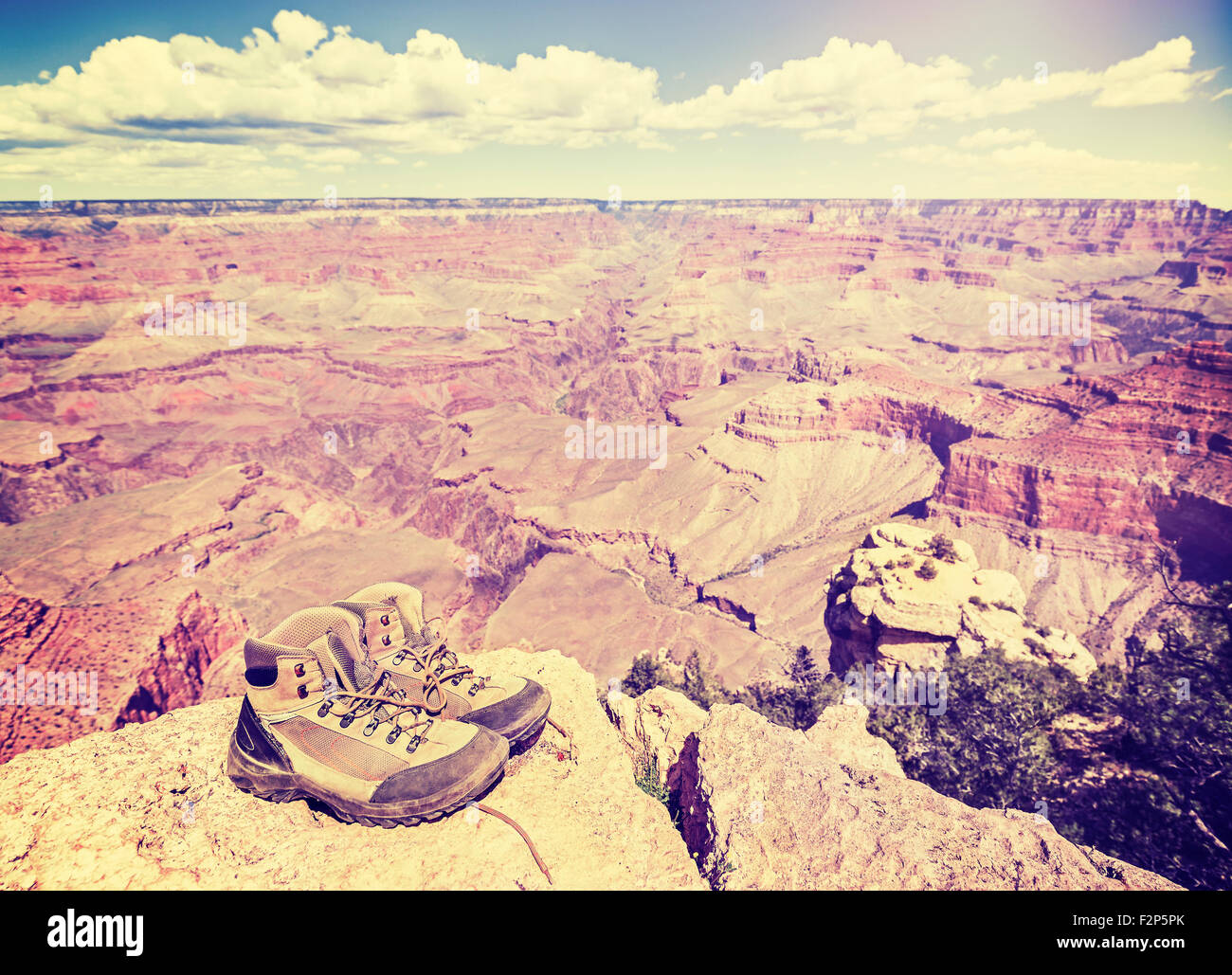 Vintage toned old trekking shoes standing on south rim of Grand Canyon, adventure concept photo. - Stock Image
