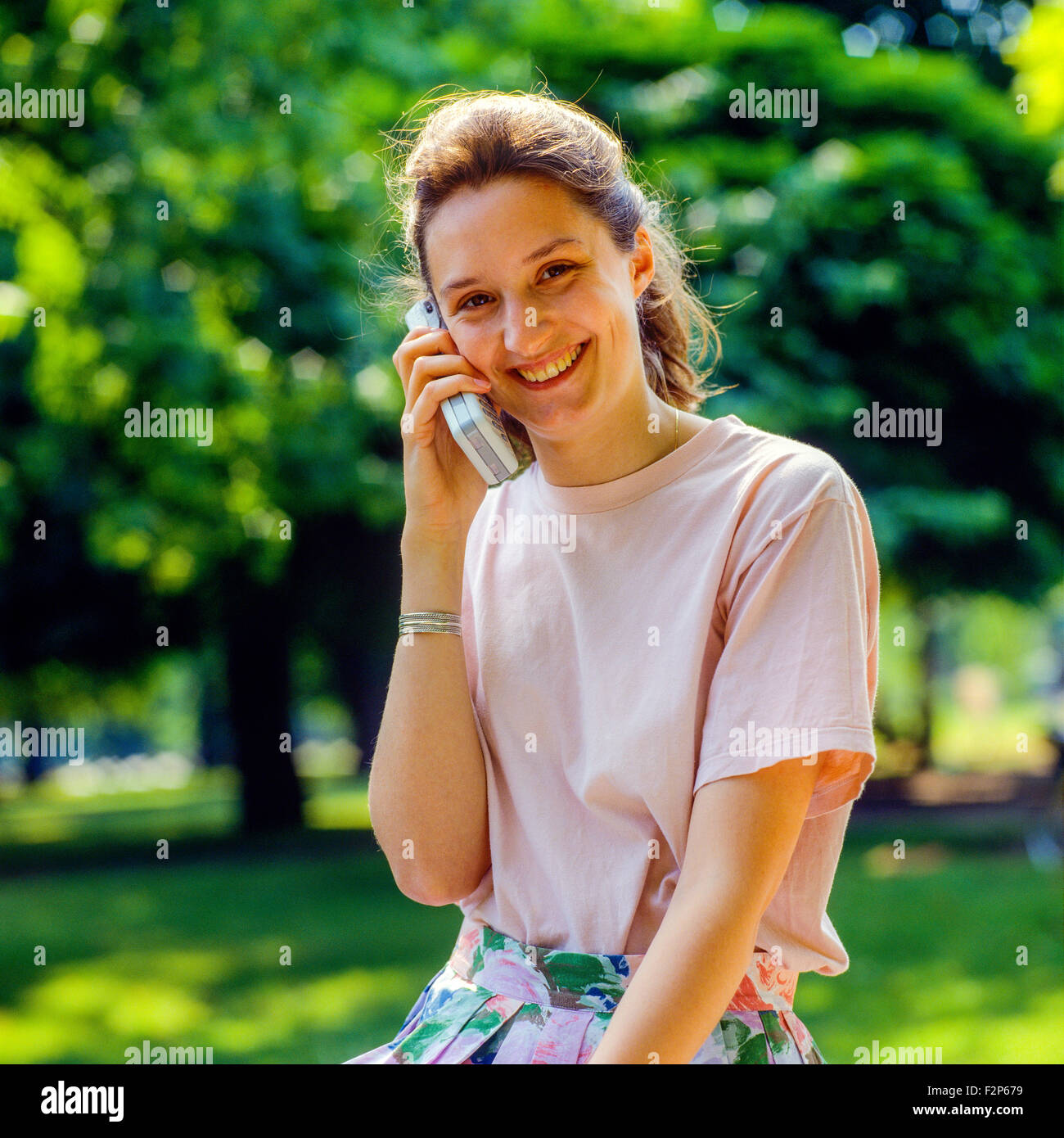 Smiling teenage girl talking on her cellular telephone in park, - Stock Image