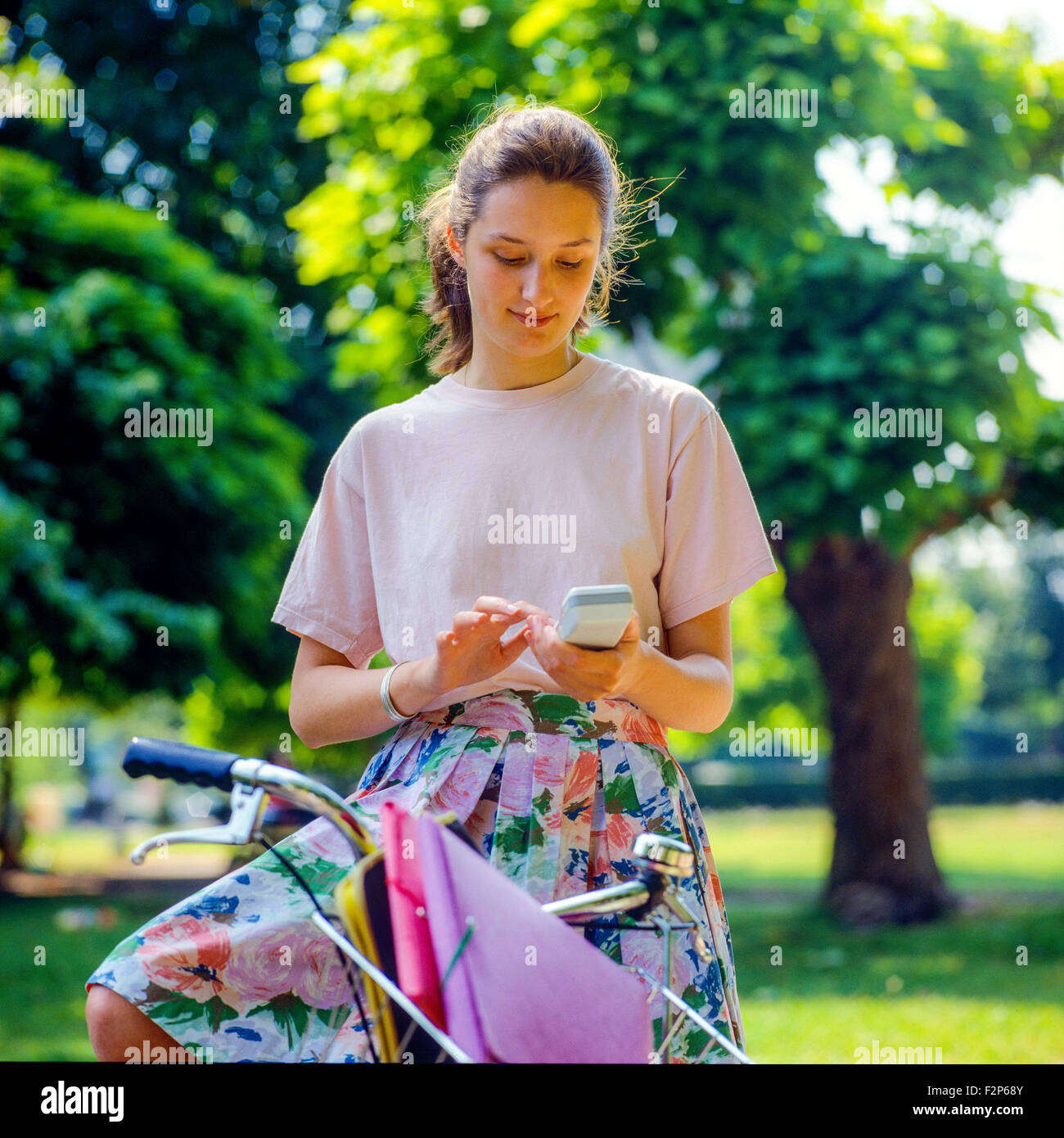 Teenage girl on her bike text messaging on her cellular telephone in park, - Stock Image
