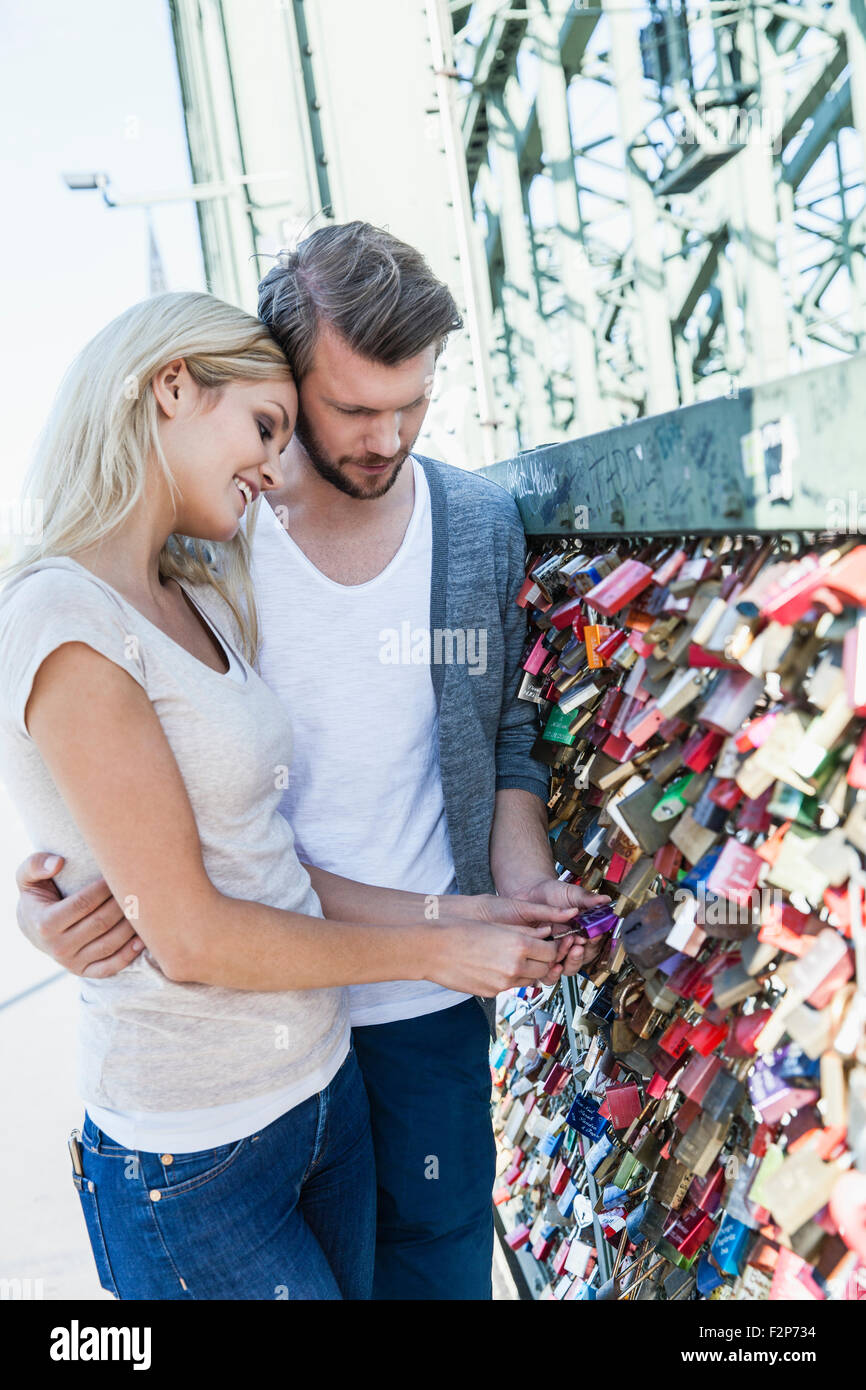 Germany, Cologne, young couple looking at love locks on  Hohenzollern Bridge - Stock Image