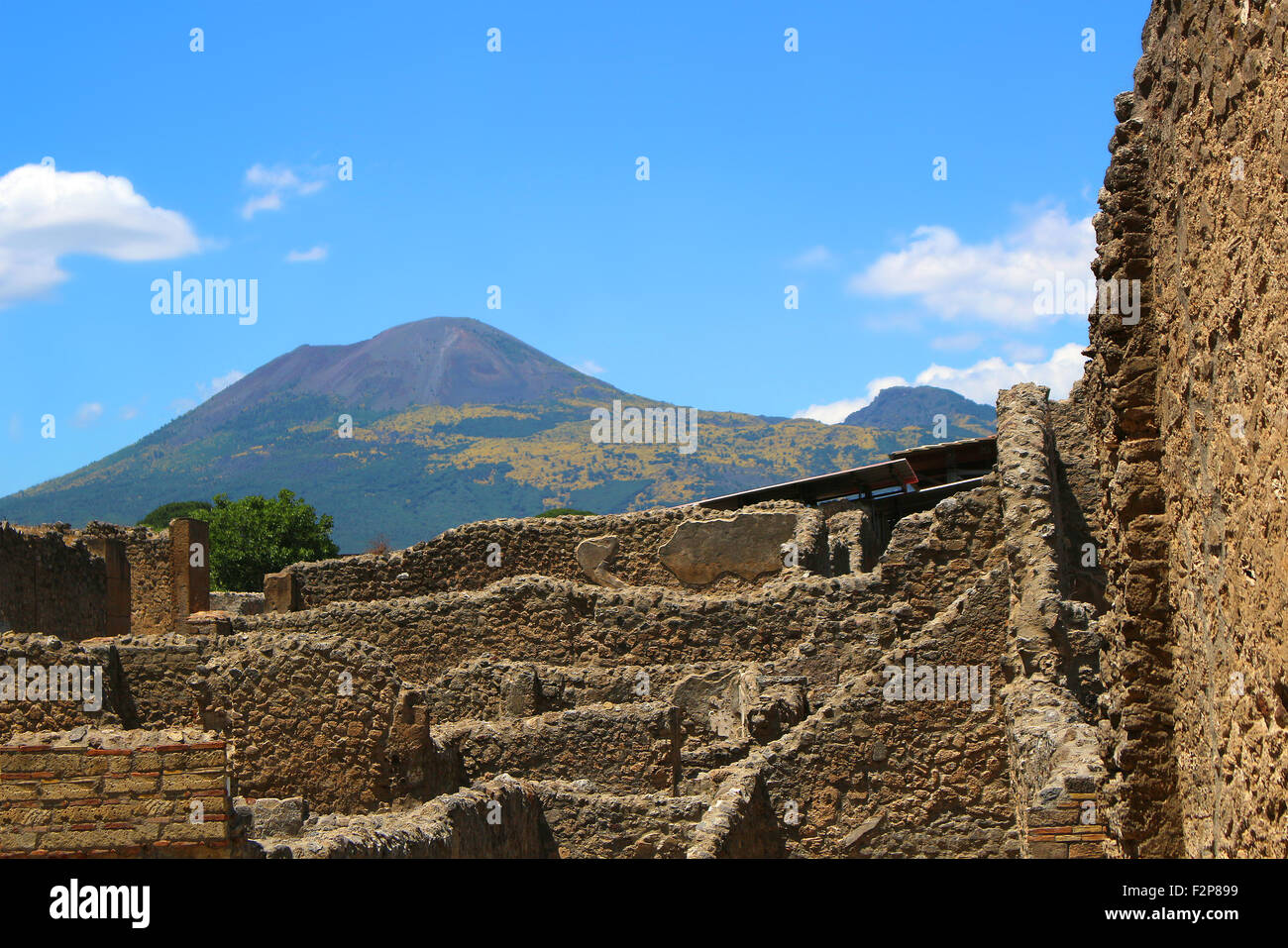 View of ruins in the old city of Pompeii, Italy with Mount Vesuvius in the background - Stock Image