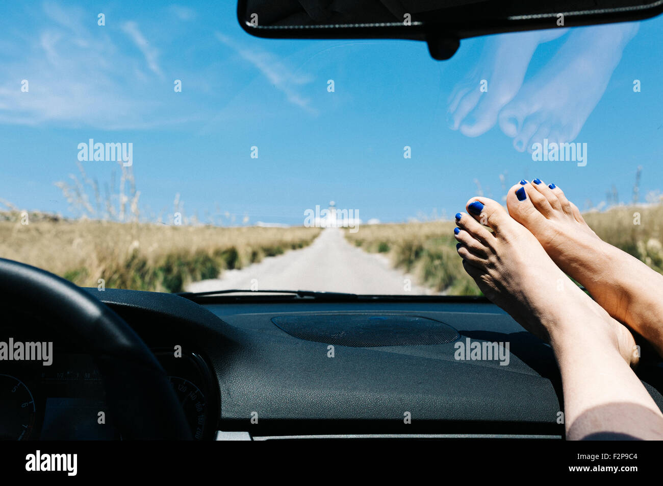 Spain, Menorca, feet on the dashboard, driving on empty road on vacations with a lighthouse in the background - Stock Image
