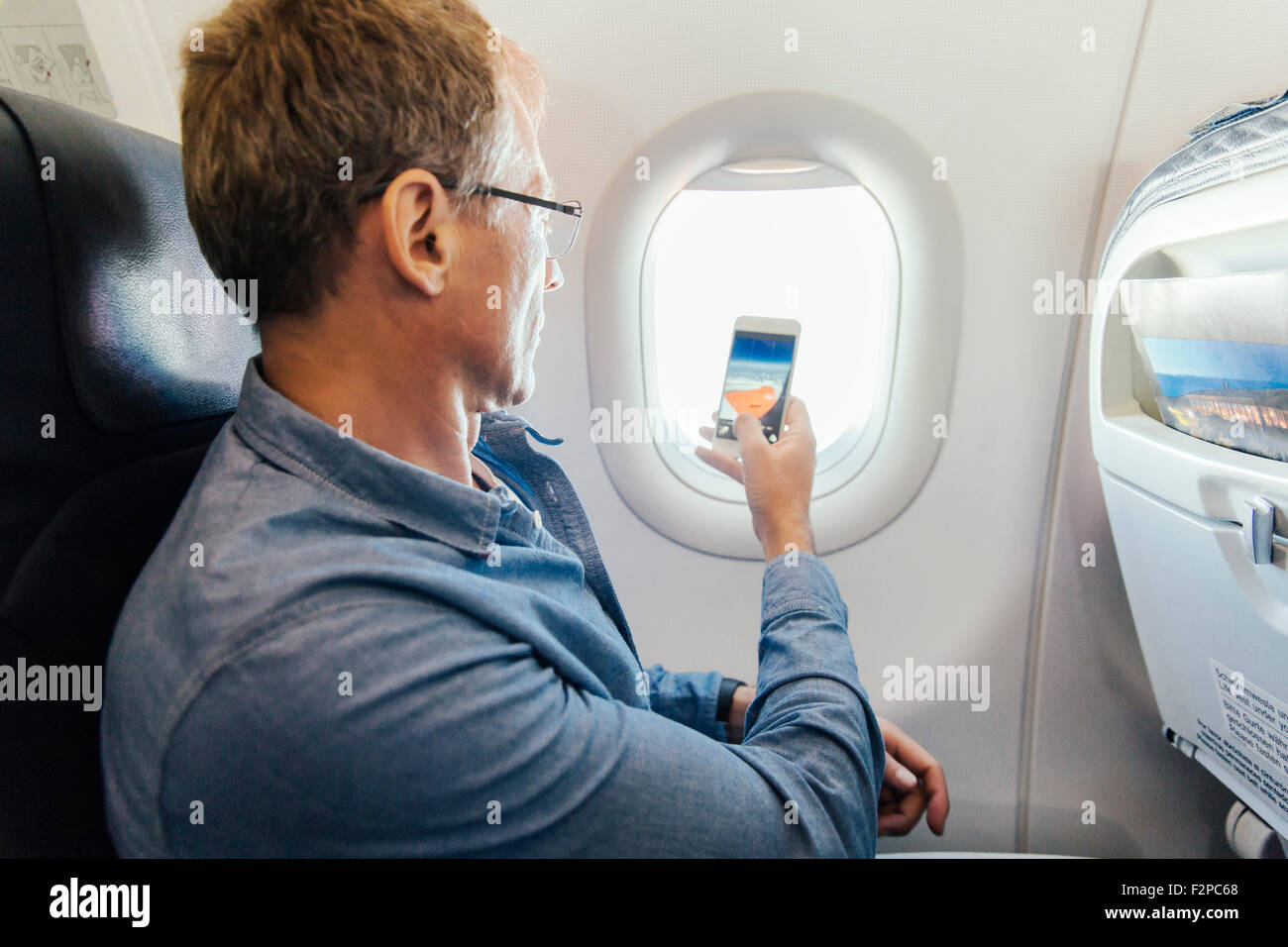 Man taking photo with his cell phone out of the window while flying on an airplane - Stock Image