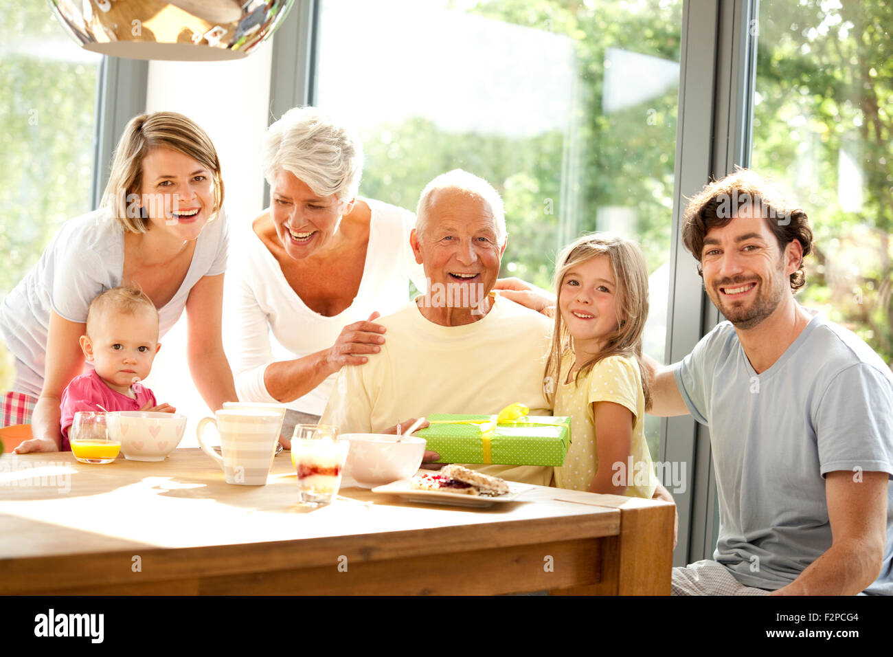 Portrait of happy extended family with present at breakfast table - Stock Image