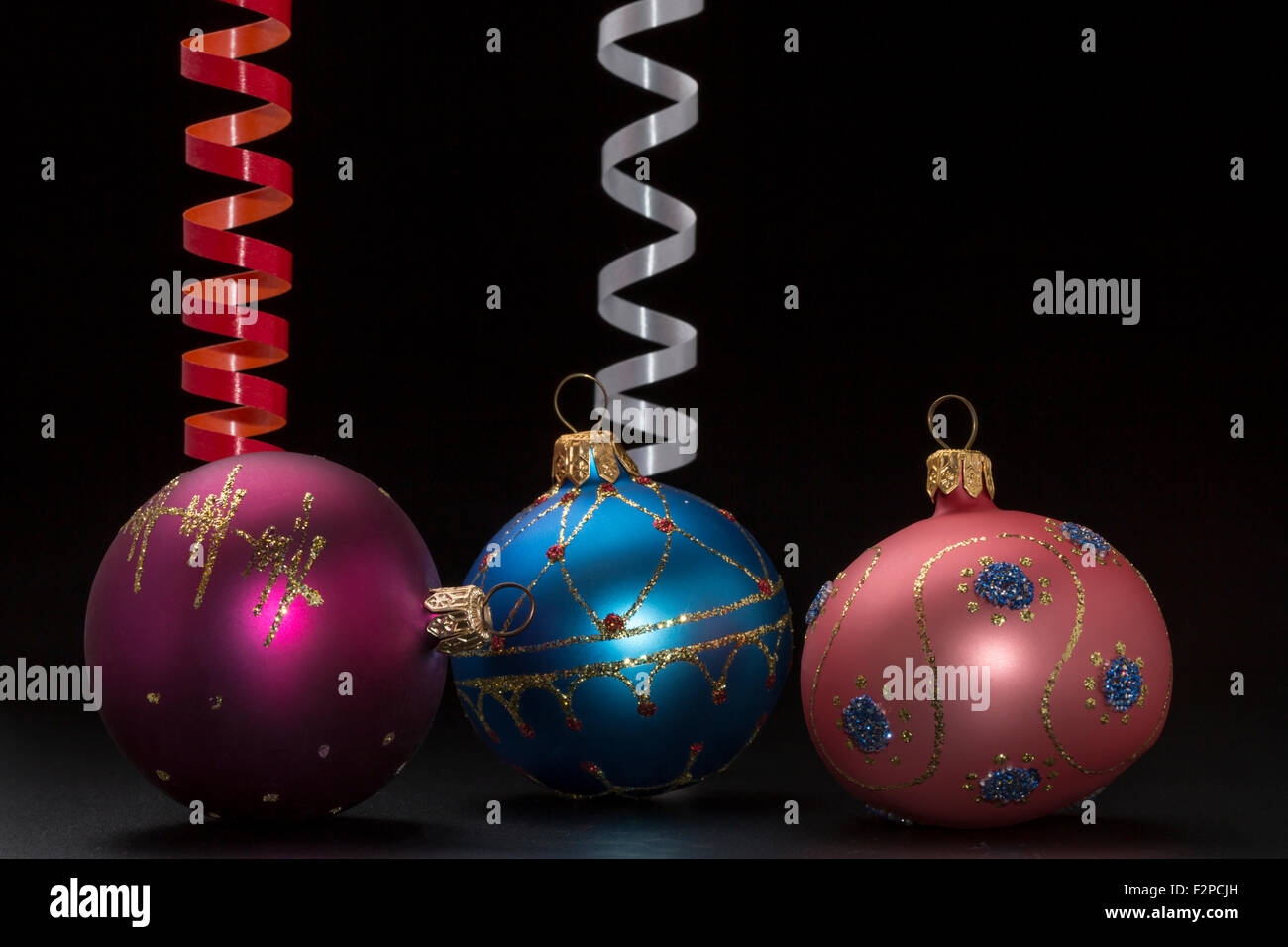 Christmas and newy year decoration with colorful balls and ribbons on black background - Stock Image