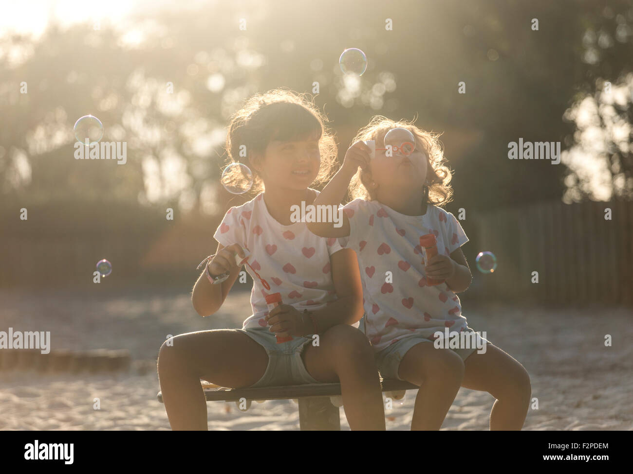 Two little sisters making soap bubbles in the park at twilight Stock Photo