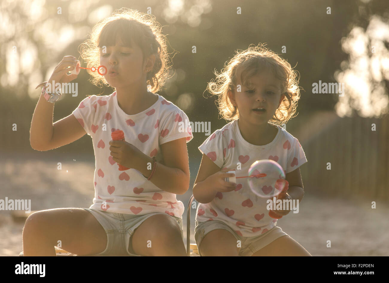 Two little sisters making soap bubbles in the park at twilight - Stock Image